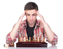Chess. Portrait of young man is playing chess covered her face. He loses Stock Photography