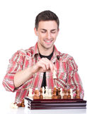 Chess. Portrait of a young smiling man is playing a chess on a white background Stock Photos