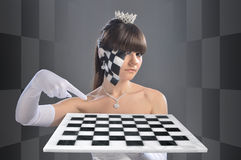 Chess queen. The girl in the image of the chess queen points to something on the chessboard, which she keeps Stock Photos