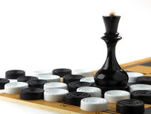 The chess queen and checkers placed on the chessboard. White background Royalty Free Stock Photo