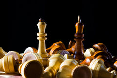 Chess queen and king on chessboard. White queen and black king among fallen chess pieces on chessboard with dark background Stock Photos