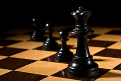 Chess queen leads pawns on chessboard. Chess board with pieces as example of game or business concept for power; strategy or success Stock Image