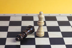 Chess queen wooden figurines fighting photo with wooden chess pieces. Stock Image