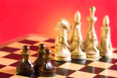 Chess on a red background. Pawn in front of the chess pieces on a red background Stock Photo