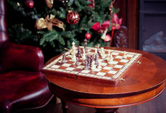 Chess set on a table with leather chair background. Blured Stock Photography