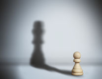 Chess shadow pawn. Chess pawn standing in a spotlight that make a shadow of king Stock Photo