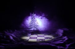 Chess in the snow. winter concept. Christmas or New Year present on a chessboard with Santa Claus on a dark background. Copy space. Selective focus Royalty Free Stock Images