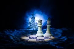 Chess in the snow. winter concept. Christmas or New Year present on a chessboard with Santa Claus on a dark background. Copy space. Selective focus Royalty Free Stock Photo