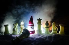 Chess in the snow. winter concept. Christmas or New Year present on a chessboard with Santa Claus on a dark background. Copy space. Selective focus Stock Photo