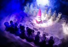 Chess in the snow. winter concept. Christmas or New Year present on a chessboard with Santa Claus on a dark background. Copy space. Selective focus Stock Photography