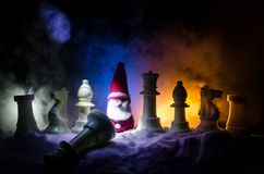 Chess in the snow. winter concept. Christmas or New Year present on a chessboard with Santa Claus on a dark background. Copy space. Selective focus Stock Image