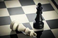 Chess Success. Checkmate black chess defeats white king on the chess board Royalty Free Stock Photo