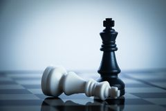 Chess Success. Checkmate black chess defeats white king on the chess board Royalty Free Stock Image