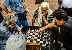 Chess sudden-death play. Four retired men in jeans playing sudden-death chess game in a public garden kalemegdan Fortress in Belgrade, Serbia in july 2014 Royalty Free Stock Photo