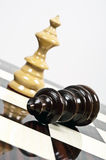 Chess table. White Queen defeat black king closeup on chessboard Royalty Free Stock Photos