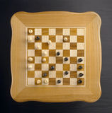 Chess table made ​​of wood. Table game of chess from wood on a gray background in studio royalty free stock photo