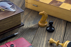 Chess on the table. Chess on a wooden table next to the book Royalty Free Stock Photo