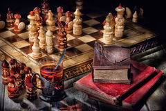 Chess, Tea And Books. Wooden crafted chess, old books and glass of tea Stock Images