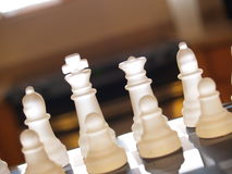 Chess Team. The king, queen, bishops, and pawns stand on a glass chess board Royalty Free Stock Image