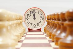 Chess time. Clock and chess figures waiting for the match Royalty Free Stock Photos