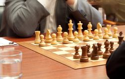 Chess tournament. Beginning of game of chess, excitement. Water glass Stock Photography