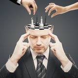 Chess tournament. Thoughtful businessman with chess board instead of brain and two businesspeople hands having a chess tournament with currency sign pawns on Stock Photos