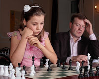 On chess training with chess trainer. Teenage girl 12-13 years old playing on chess training with chess trainer watching her Stock Photography