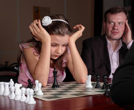 On chess training with chess trainer. Teenage girl 12-13 years old playing on chess training with chess trainer watching her Royalty Free Stock Image