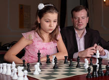On chess training with chess trainer. Teenage girl 12-13 years old playing on chess training with chess trainer watching her Royalty Free Stock Photography