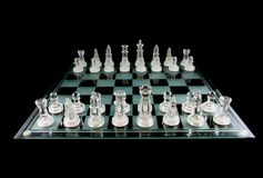 Chess in the Void. Glass Chess Pieces on a Frosted Glass Chess Board fully isolated on black Stock Photo