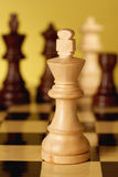 Chess white king. Is in focus, game of chess comes to an end. when the king is checkmated, and the other party is victorious Royalty Free Stock Photo