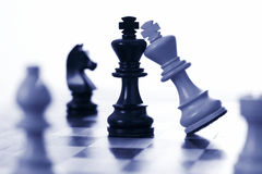 Chess white king attacks black king. Blue tone stock image