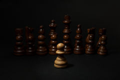 Chess. White pawn and Black figures on black background. Set of black figures. Royalty Free Stock Images