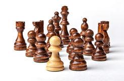 Chess. White pawn and Black figures on white background. Royalty Free Stock Images