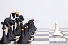 Chess white pawn in front of black pieces Stock Images