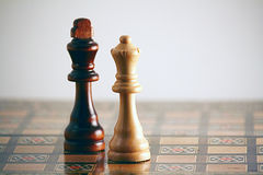 Chess - White Queen and black King 2. White Queen meets black King on an ornate wooden chess board royalty free stock images