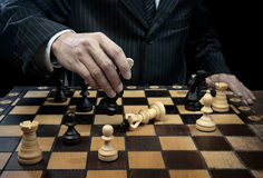 Chess winner. Businessman plays chess and win the game Royalty Free Stock Images
