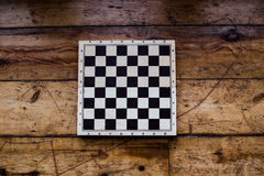 Chess on a wooden board set on some wooden floor. Wooden chess board set on some old wooden floor. No pieces set Royalty Free Stock Images