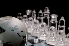 Chess world. Crystal chess pieces on against a globe Stock Photography