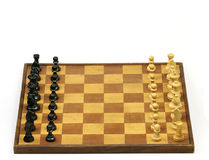 Chessboard. Old and aged wooden chessboard with chess pieces on a white background Stock Photos