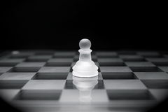 Chessboard_9. Glass pawn on a chessboard generally symbolizing service and subordination but also teamwork Royalty Free Stock Photo