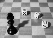 Chessboard with black king and three dices stock photo