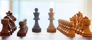 Chess board blurred with chess pieces on it. Close up view with details, white background. stock photo