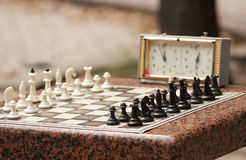 Chessboard with chess. And timer in the park Royalty Free Stock Photo