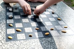 Chessboard for chess or outdoor checkers in the park. A place in the park to play in check or checkers. Outdoor fun in the park on a sunny spring day. He plays stock photography