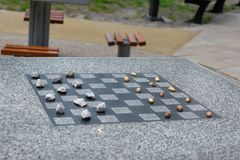 Chessboard for chess or outdoor checkers in the park. A place in the park to play in check or checkers. Outdoor fun in the park on a sunny spring day. He plays stock photo