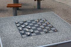 Chessboard for chess or outdoor checkers in the park. A place in the park to play in check or checkers. Outdoor fun in the park on a sunny spring day. He plays royalty free stock photo