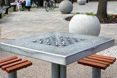 Chessboard for chess or outdoor checkers in the park. A place in the park to play in check or checkers. Outdoor fun in the park on a sunny spring day. He plays stock photos