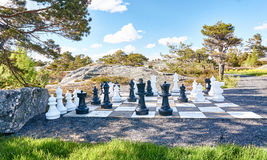 Chessboard and chess outdoors. Chessboard made of concrete panels. Plastic large chess pieces on the outside. Around conifers, pines. Norwegian landscape Stock Images