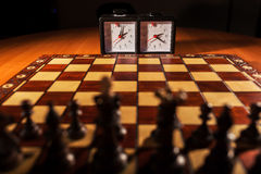 Chessboard, clock and figures Stock Photo